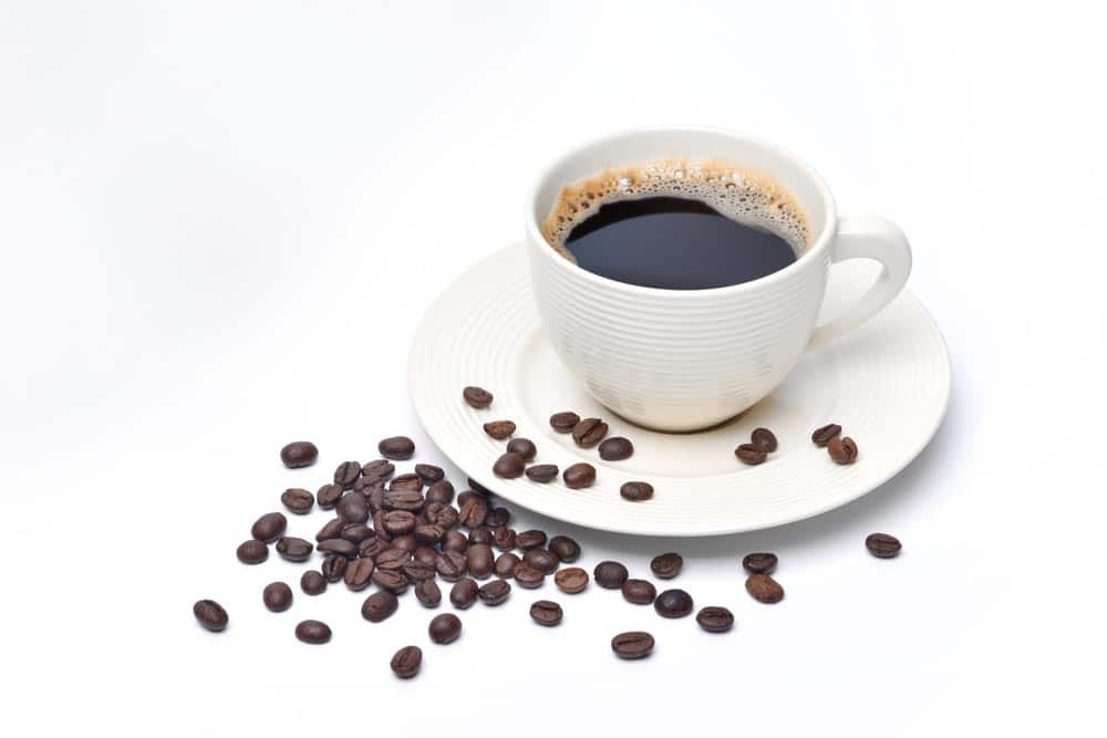 image of white cup of coffee and coffee beans on white background