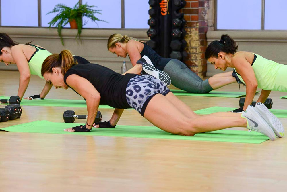 image of Cathe Friedrich, Brenda, Jenn and Jai doing a push up on their knees in Cathe's Fit Split workout