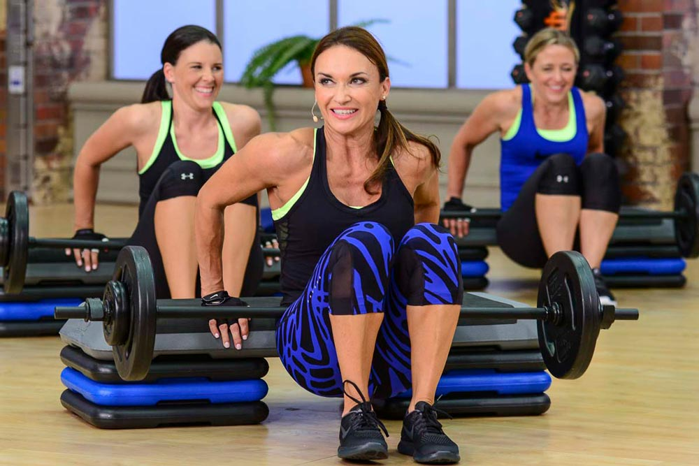 image of Cathe, Jenn and Brenda doing dips on a bench with a weighted barbell