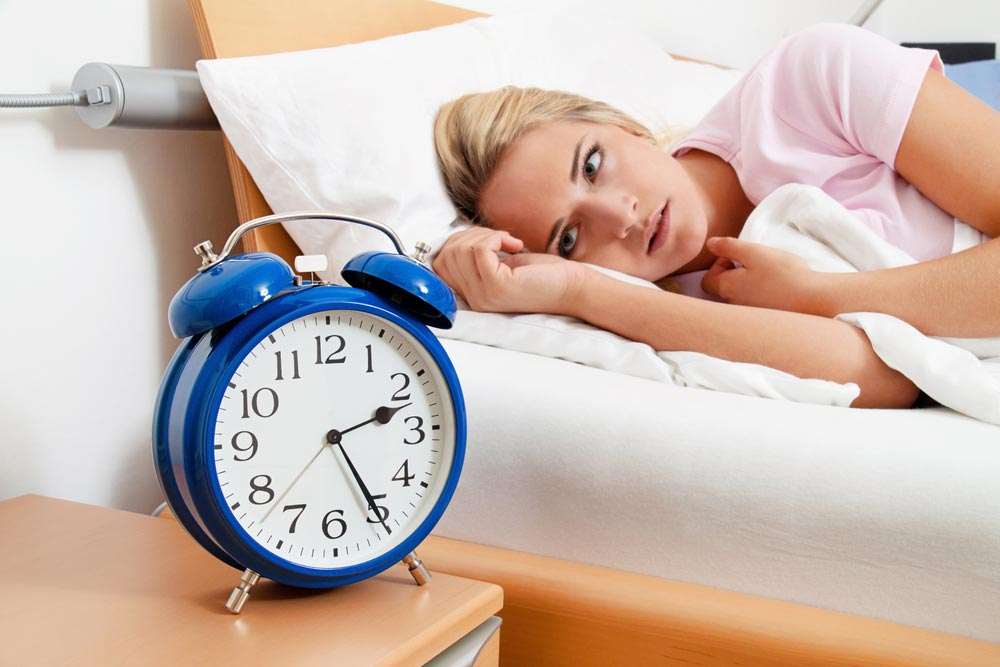 A woman having a problem sleeping. Can lack of sleep increase the risk of a training injury?