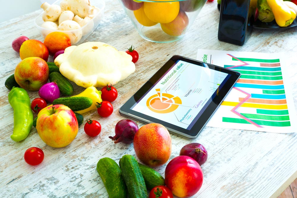 image of organic food and a Tablet PC showing information about healthy nutrition and phytochemical composition.