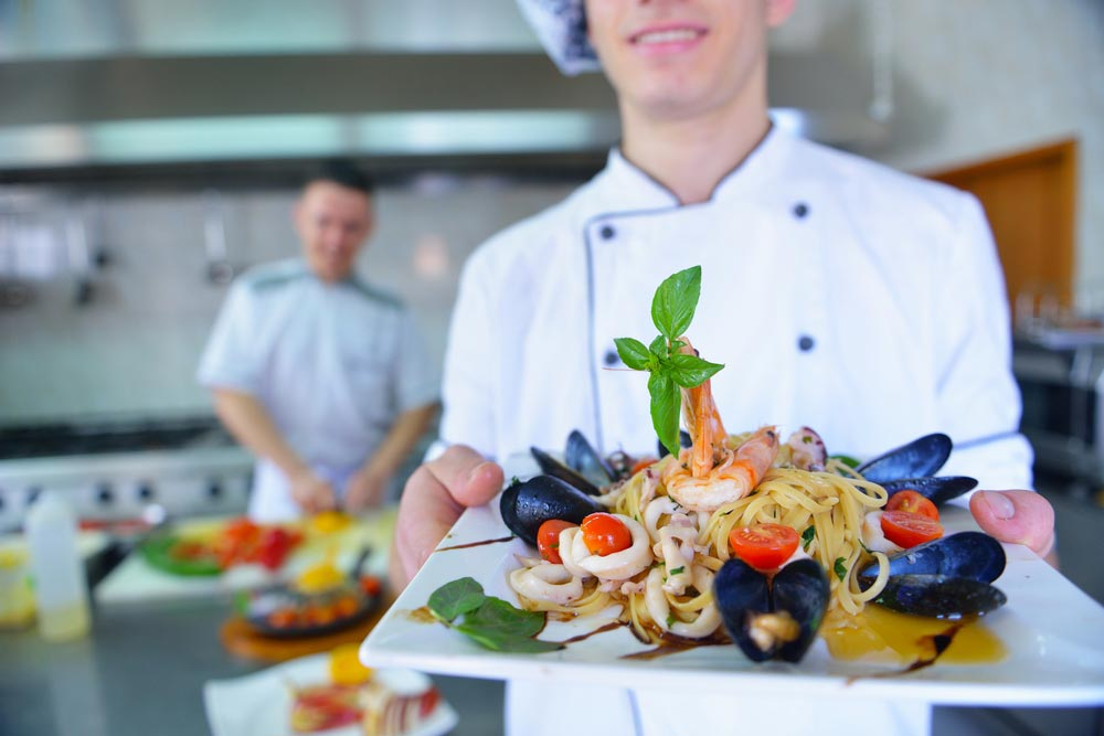 image of a chef dressed in white uniform decorating pasta salad and seafood fish in modern kitchen