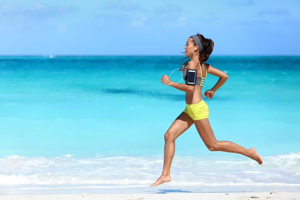 image of female exercising in the heat running barefoot with determination under summer sun in hot weather.