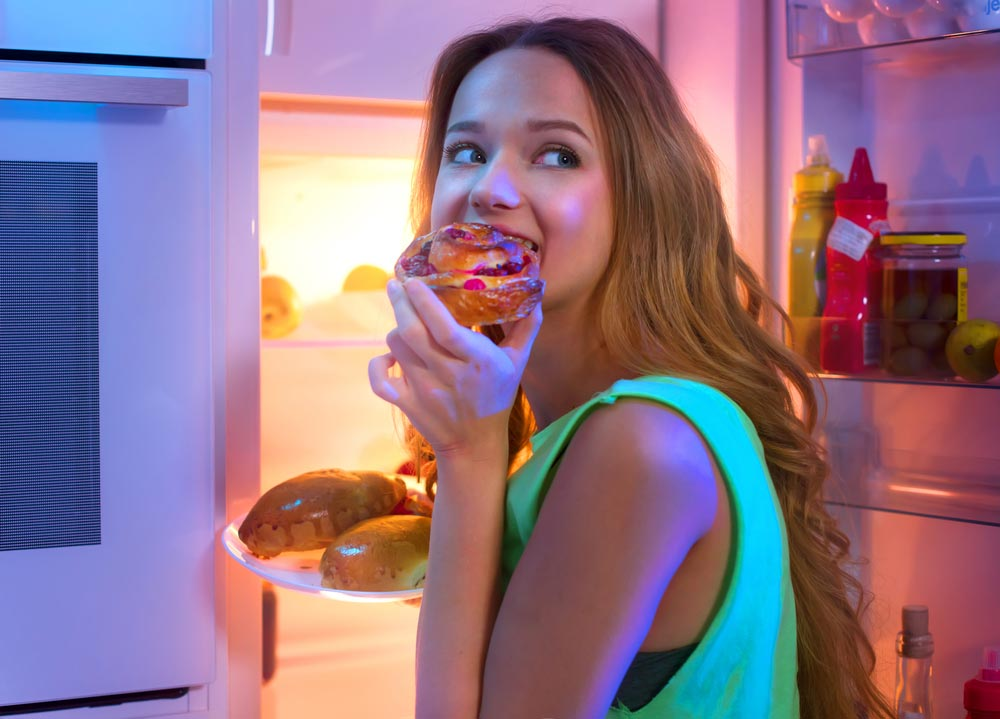 image of a young woman with an appetite late at night eating an unhealthy snack from the refrigerator
