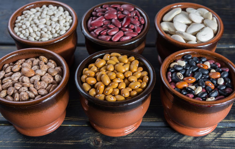 image of an assortment of beans on black wooden background. Soybean, red kidney bean, black bean,white bean, red bean and brown pinto beans