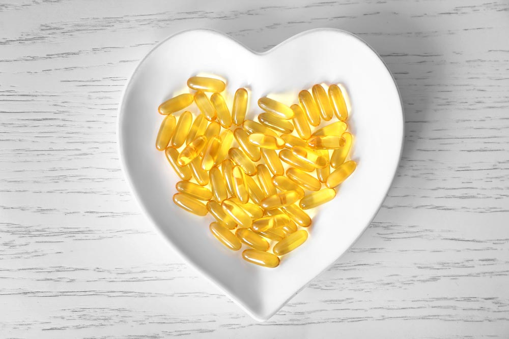 image of Heart-shape plate with fish oil capsules on wooden background