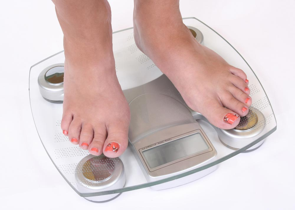 A pair of female feet standing on scale determining her body weight which could impact her risk of getting type 2 diabetes.