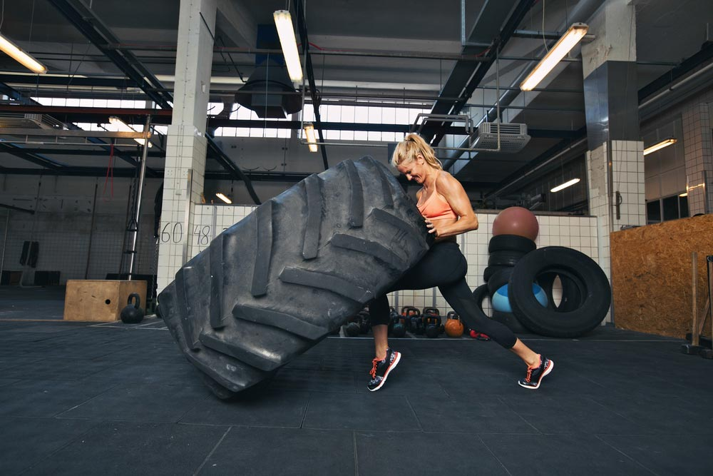 Fit female athlete working out with a huge tire, turning and flipping in the gym. Can extrem exertion cause rhabdomyolysis?