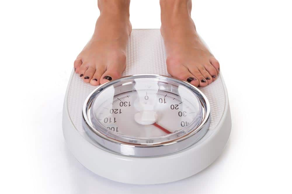 A woman standing on weighing scale.