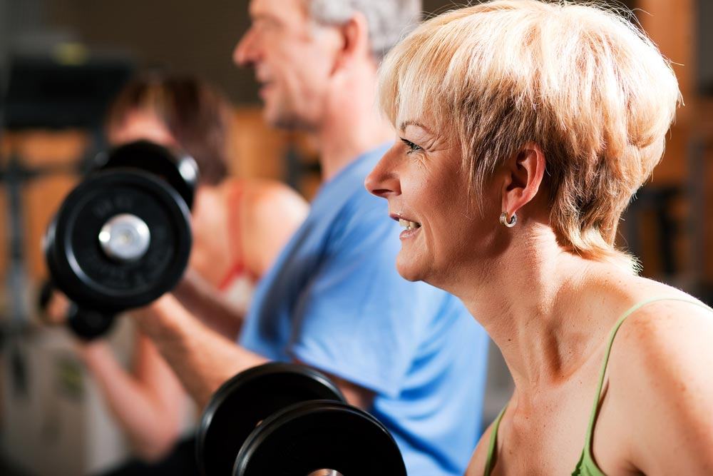 Senior exercise lifting weights which helps improve their quality of life and reduce the risk of dying prematurely.
