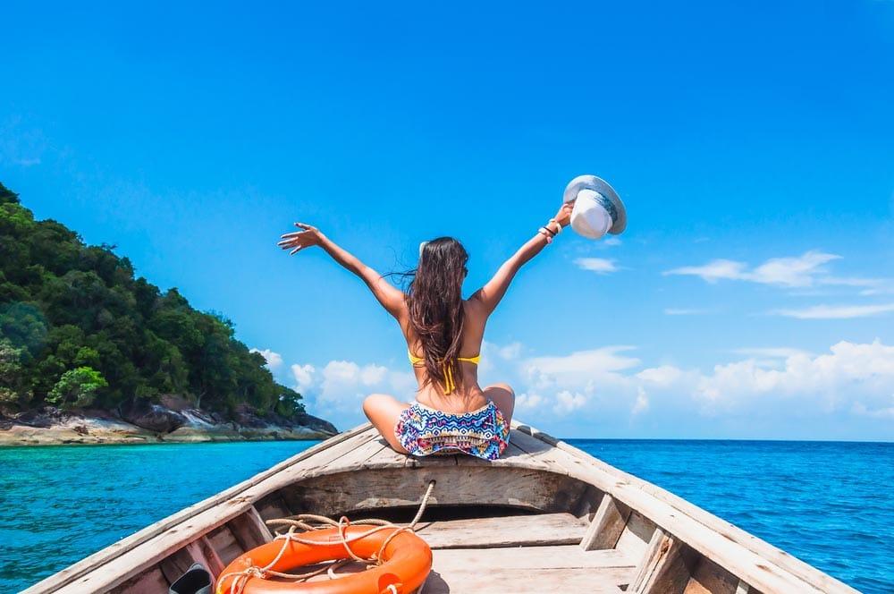 Happy woman traveler in bikini relaxing on boat enjoying her summer vacation