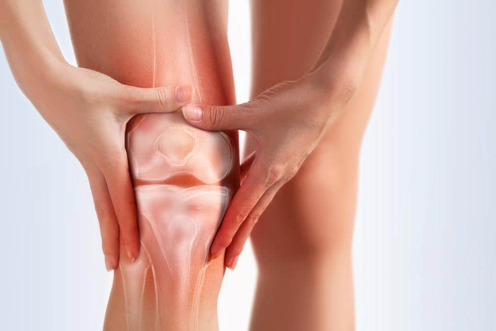 Woman in pain from knee osteoarthritis grabbing her knee