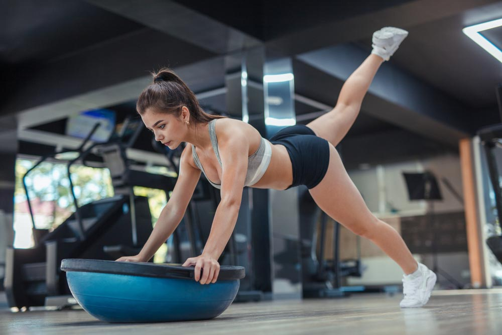 Young woman leaning on bosu ball and lifting legs with great concentration as she works on her balance skills.