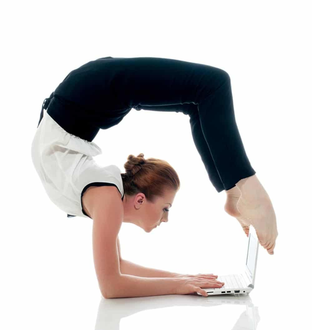 Businesswoman demonstrating flexibility doing yoga and typing on netbook