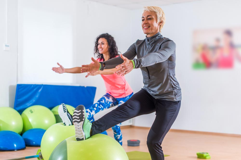 Group of active cheerful sporty women doing single-leg squats with balance ball training indoors in gym.