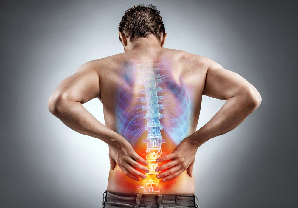 Back view of a male having lower back pain cause by spine alignment problems
