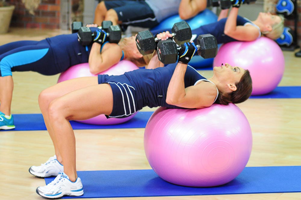 Cathe Friedrich on a pink stability ball strength training doing a close grip dumbbell bench press